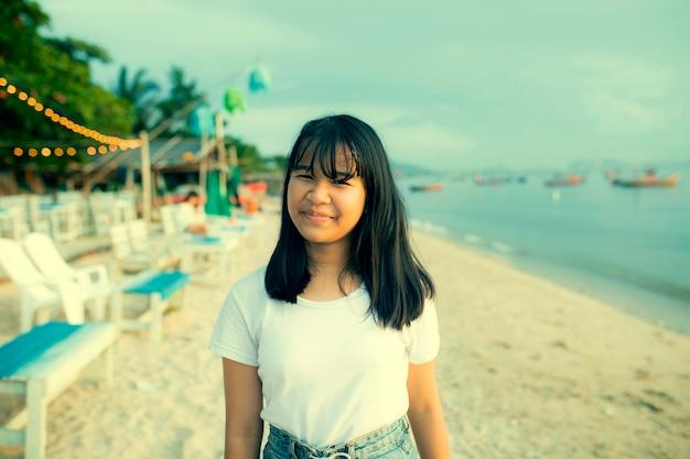 Lächelndes gesichtsglück des asiatischen jugendlichen auf sommerferien-seestrand