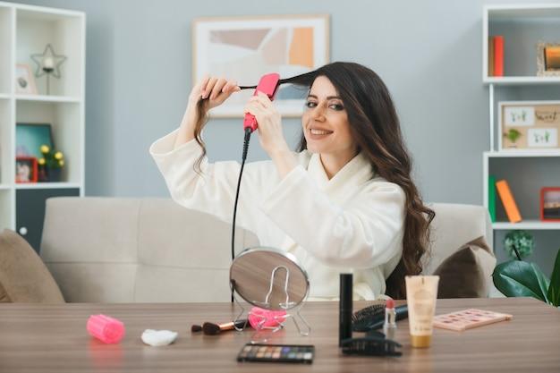 Lächelndes glätten haar mit flachem eisen junges mädchen sitzt am tisch mit make-up-tools im wohnzimmer