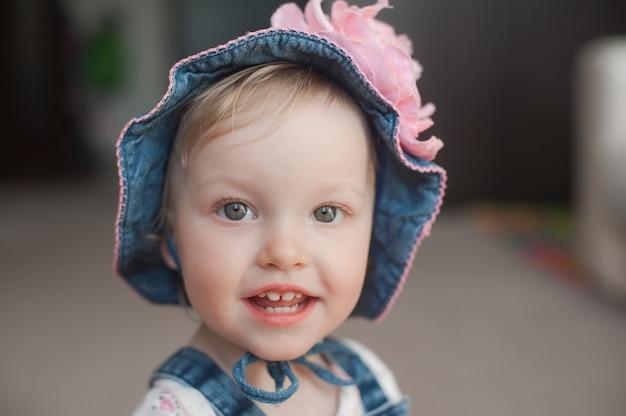 Lächelndes glückliches baby im sommerhut. panama mit einer großen rosa blume.