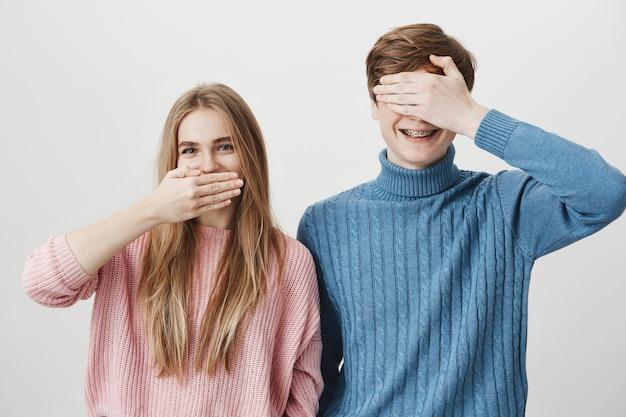 Lächelndes glückliches blondes mädchen bedecken mund und kerl schließen augen mit hand