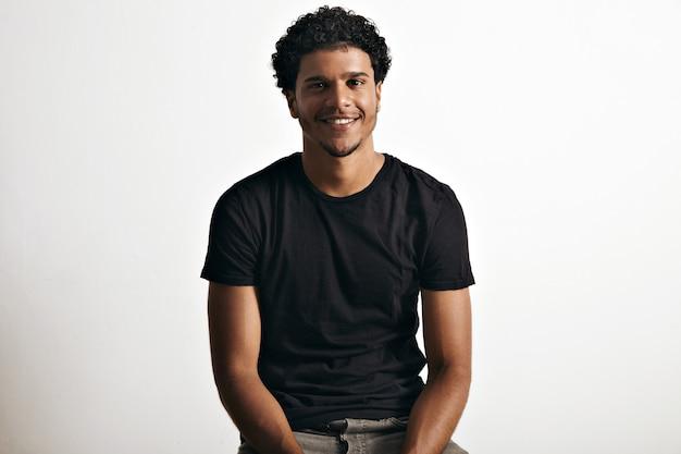 Lächelndes glückliches gesundes afroamerikanisches modell, das ein leeres kurzärmeliges baumwoll-t-shirt trägt, das auf weiß lokalisiert wird
