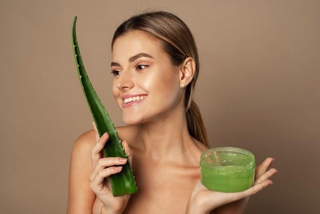 Lächelndes glückliches junges weibliches modell, das aloe-blatt und glas aloe-gel auf beigem hintergrund hält. das konzept der hautpflege, die mit naturkosmetik befeuchtet.