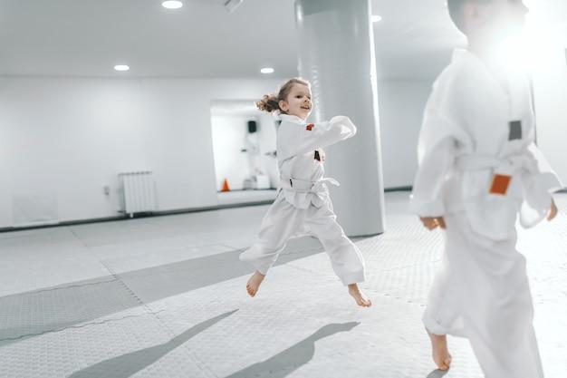 Lächelndes glückliches kaukasisches kleines mädchen, das am taekwondo-training springt und dobok trägt.