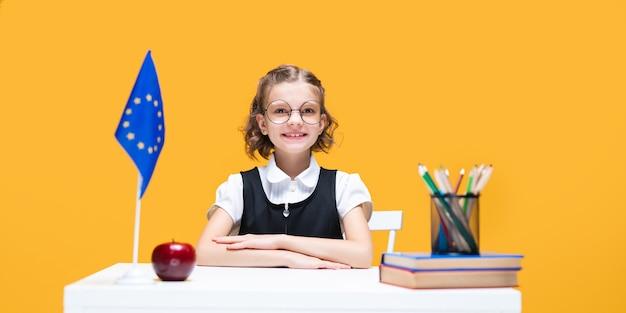 Lächelndes glückliches kaukasisches schulmädchen, das während des englischunterrichts am schreibtisch sitzt flagge der europäischen union