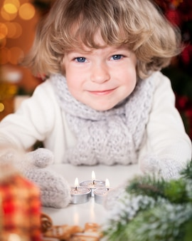 Lächelndes glückliches kind mit weihnachtskerzen und -dekorationen. fokus auf kerzen