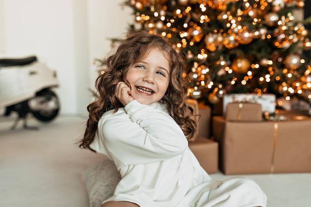 Lächelndes glückliches kleines mädchen mit lockigem haar, das weißen gestrickten pullover trägt, der mit glücklichem lächeln beim sitzen des weihnachtsbaumes aufwirft