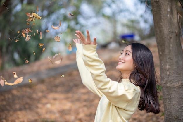 Lächelndes glückliches mädchen der schönen asiatin und tragendes warmes kleidungswinter- und -herbstporträt an im freien im park