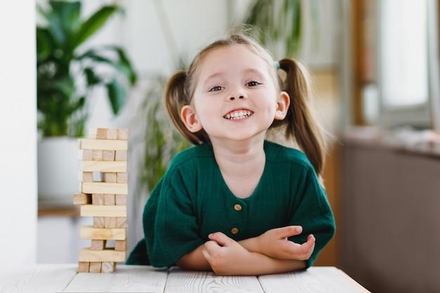Lächelndes glückliches mädchen im vorschulalter, das jenga spielt und zu hause lustig und fröhlich auf dem spiel bleibt