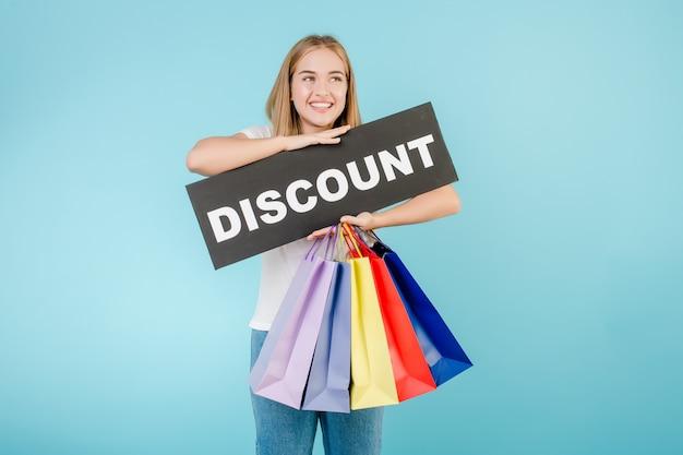 Lächelndes glückliches mädchen mit dem rabattzeichen und bunten einkaufstaschen lokalisiert über blau
