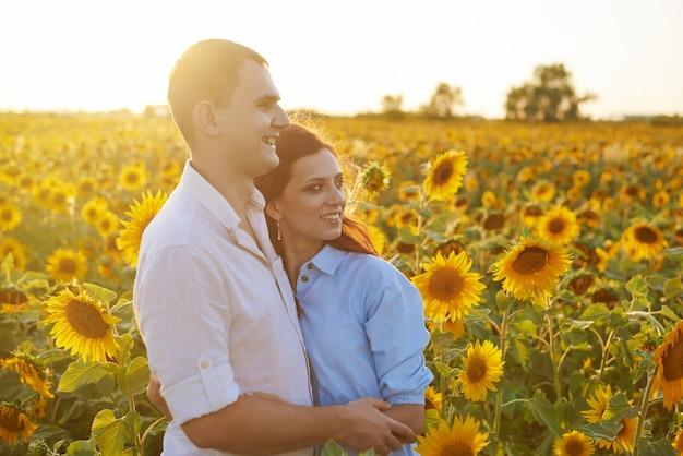 Lächelndes glückliches paar, das in einem feld mit sonnenblumen umarmt