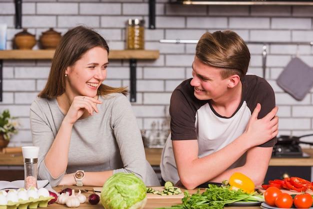 Lächelndes glückliches paar, das zusammen in der küche kocht