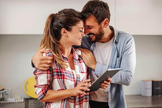 Lächelndes glückliches paar, das zusammen in der küche steht und tablette verwendet, um nach rezept zu suchen.
