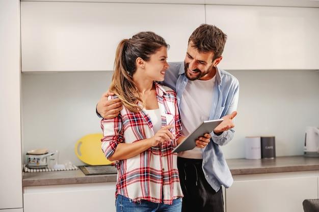 Lächelndes glückliches paar, das zusammen in der küche steht und tablette verwendet, um nach rezept zu suchen