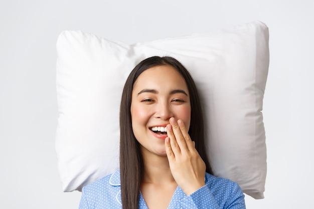 Lächelndes glückliches schönes asiatisches mädchen, das im bett auf kissen im blauen pyjama liegt, offene augen aufwacht und gähnt, morgenroutine der jungen frau. nettes weibchen in jammies, das im bett bleibt, weißer hintergrund