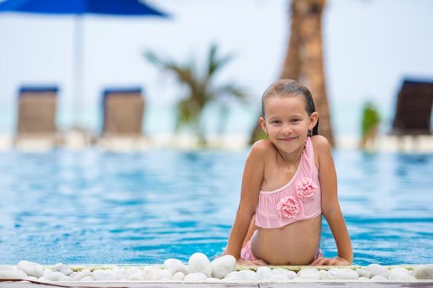 Lächelndes glückliches schönes mädchen, das spaß swimmingpool im im freien hat