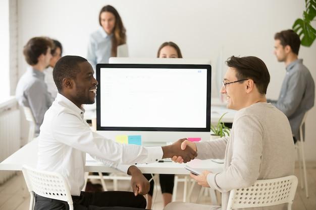 Lächelndes händeschütteln der verschiedenen kollegen, das die erfolgreiche teamarbeit feiert und für hilfe dankt