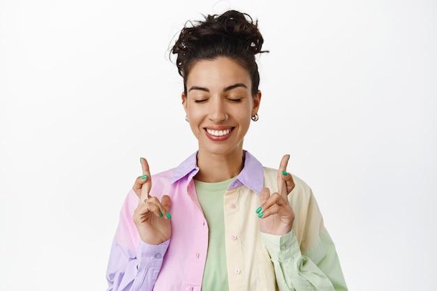 Lächelndes hoffnungsvolles brünettes mädchen macht wünsche, kreuzt die finger und schließt die augen, erwartet ergebnisse, wartet darauf, dass ein traum wahr wird, betet, steht auf weiß