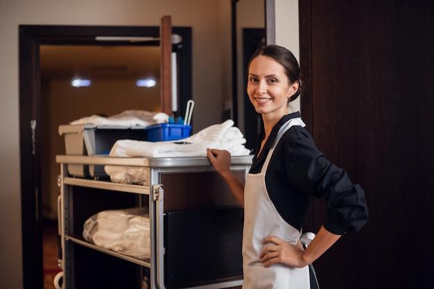 Lächelndes hotelmädchen mit frischen handtüchern beim housekeeping