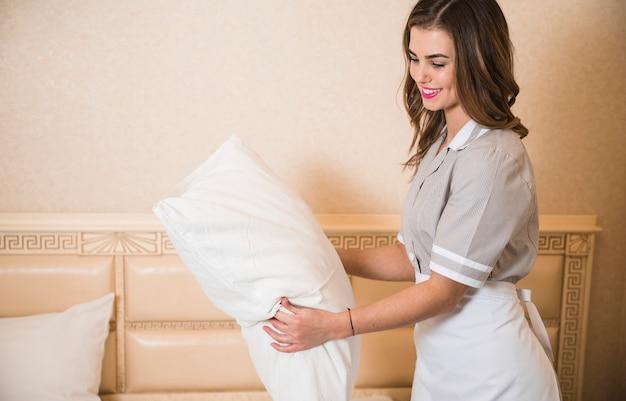 Lächelndes hotelpersonal, das weißes kissen im hotelzimmer errichtet