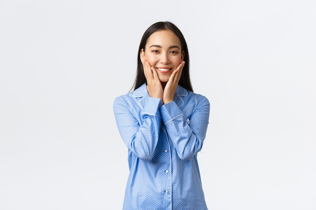 Lächelndes hübsches asiatisches mädchen, das saubere haut berührt