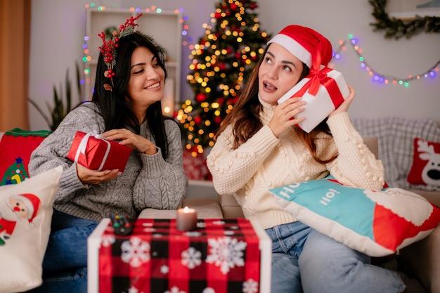 Lächelndes hübsches junges mädchen mit stechpalmenkranz hält geschenkbox und sieht ihre freundin mit weihnachtsmütze auf einem sessel sitzen und genießt die weihnachtszeit zu hause