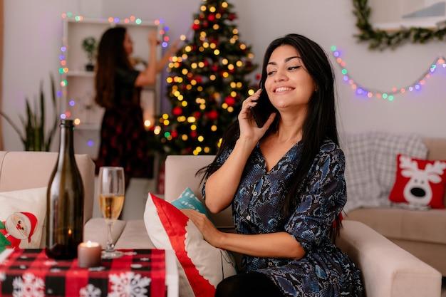 Lächelndes hübsches junges mädchen spricht am telefon, das auf sessel sitzt und ihre freundin schmückt weihnachtsbaum hinter, der weihnachtszeit zu hause genießt