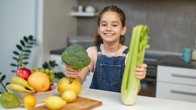 Lächelndes hübsches kleines mädchen steht in der nähe des tisches in der küche und hält grünen brokkoli und sellerie in den händen.