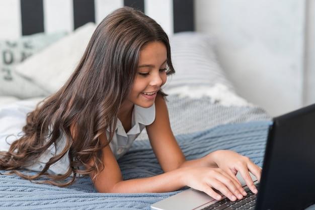 Lächelndes hübsches mädchen, das auf bett unter verwendung des laptops liegt