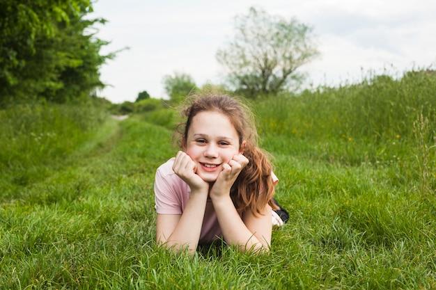 Lächelndes hübsches mädchen, das auf grünem gras am park liegt