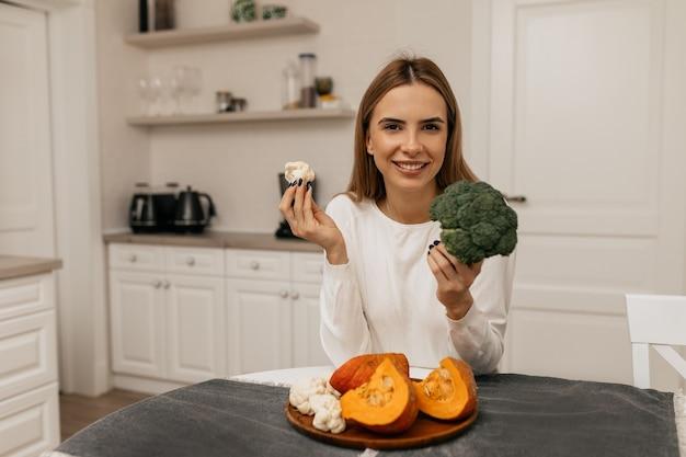 Lächelndes hübsches mädchen, das das kochen mit gemüse in der küche vorbereitet