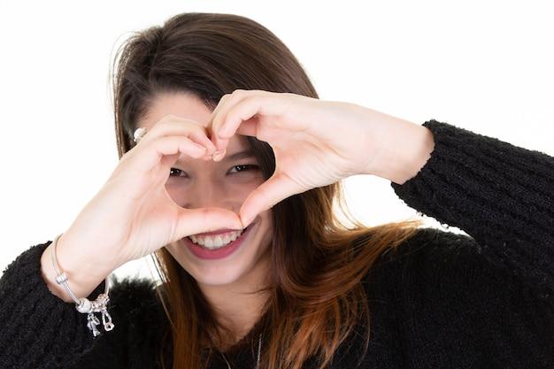 Lächelndes hübsches mädchen, das herzgeste mit handvordergesichtsaugen zeigt