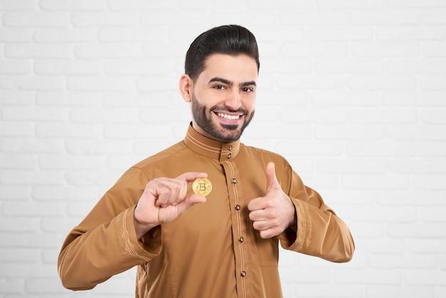 Lächelndes hübsches moslemisches modell in der traditionellen islamischen kleidung, die mit goldenem bitcoin aufwirft