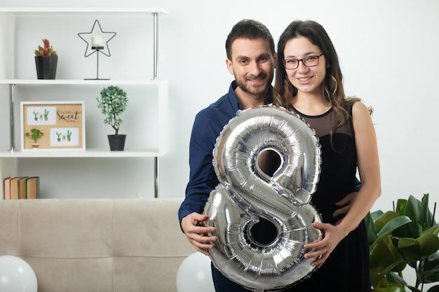 Lächelndes hübsches paar, das am internationalen frauentag im märz acht ballons hält, die im wohnzimmer stehen?