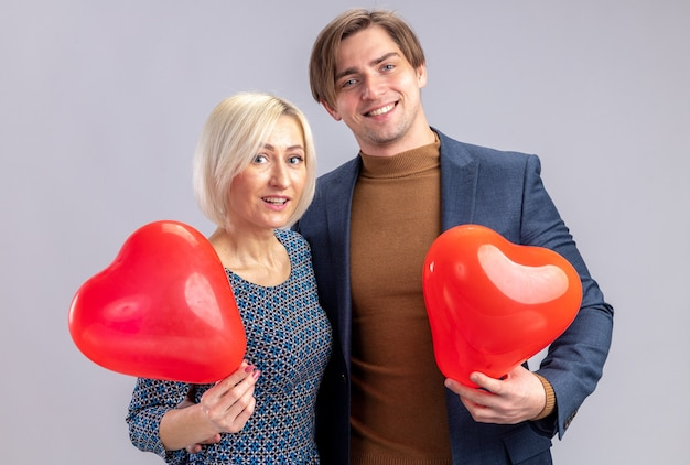 Lächelndes hübsches paar mit roten luftballons in herzform am valentinstag