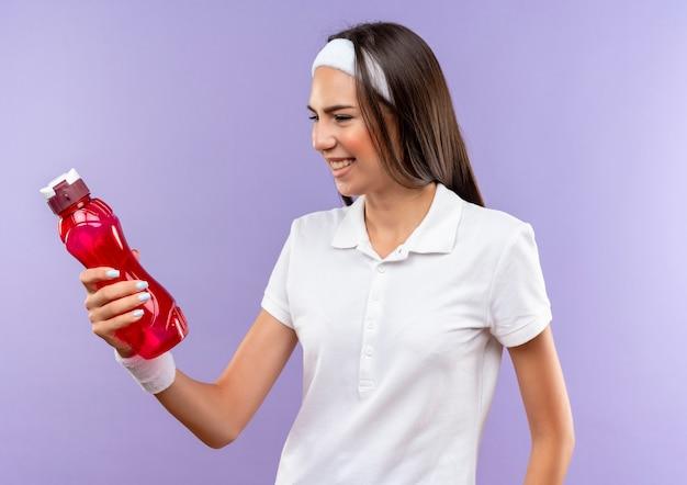 Lächelndes hübsches sportliches mädchen, das stirnband und armband trägt und wasserflasche lokalisiert auf lila raum hält