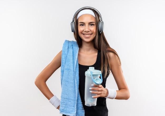 Lächelndes hübsches sportliches mädchen, das stirnband und armband und kopfhörer trägt wasserflasche mit handtuch auf schulter lokalisiert auf weißem raum trägt Kostenlose Fotos