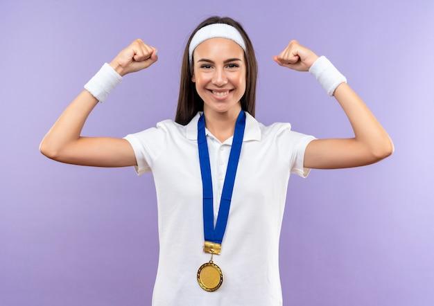 Lächelndes hübsches sportliches mädchen, das stirnband und armband und medaille gestikuliert stark gestikuliert auf lila raum