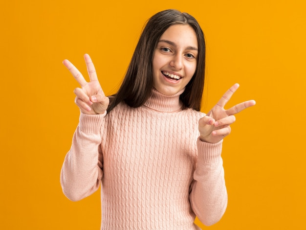 Lächelndes hübsches teenager-mädchen, das nach vorne schaut und mit beiden händen ein friedenszeichen macht, isoliert auf oranger wand mit kopierraum?