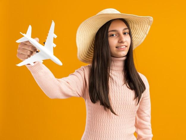 Lächelndes hübsches teenager-mädchen mit strandhut, das modellflugzeug isoliert auf orangefarbener wand hält