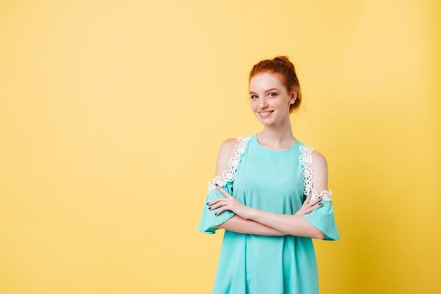 Lächelndes ingwermädchen im kleid, das mit verschränkten armen aufwirft und schaut
