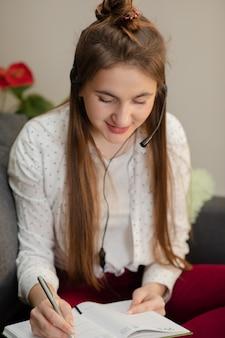 Lächelndes jugendlich mädchen, das kopfhörer trägt, die audiokurs hören, der notizen macht, junge frau, die fremdsprachen lernt, digitale selbstbildung, online studiert, musik genießt.