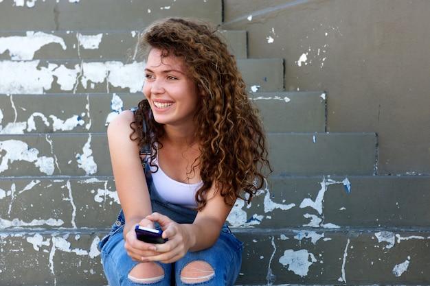 Lächelndes jugendlich mädchen, das telefon hält und auf schritten sitzt