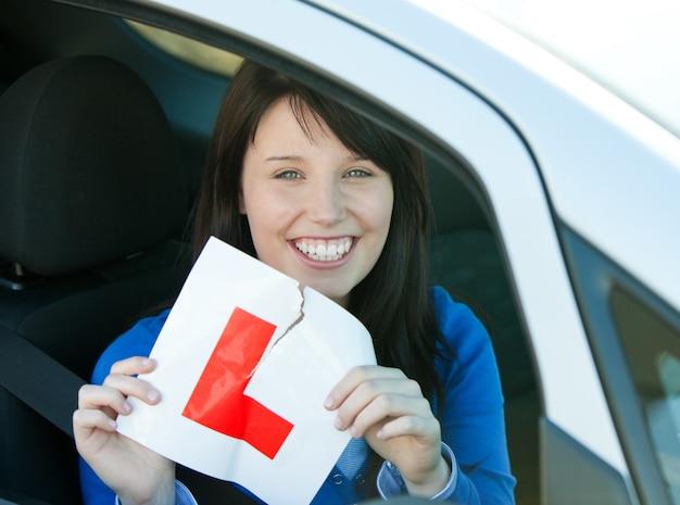 Lächelndes jugendlich mädchen des brunette, das in ihrem auto reißt ein l-zeichen sitzt