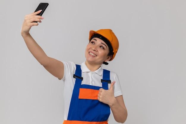 Lächelndes junges asiatisches baumeistermädchen mit orangefarbenem schutzhelm, das nach oben greift und selfie am telefon macht