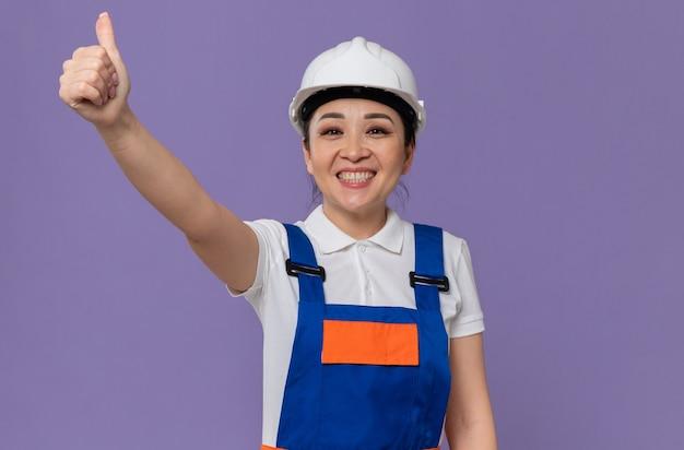 Lächelndes junges asiatisches baumeistermädchen mit weißem schutzhelm, der nach oben greift