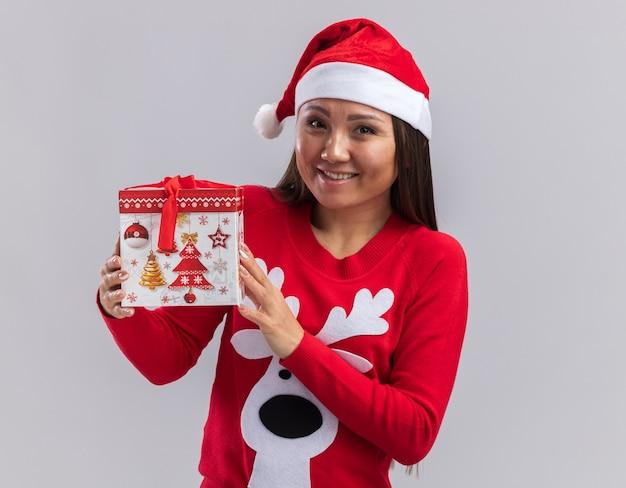 Lächelndes junges asiatisches mädchen, das weihnachtsmütze mit pullover hält geschenkbox lokalisiert auf weißem hintergrund trägt