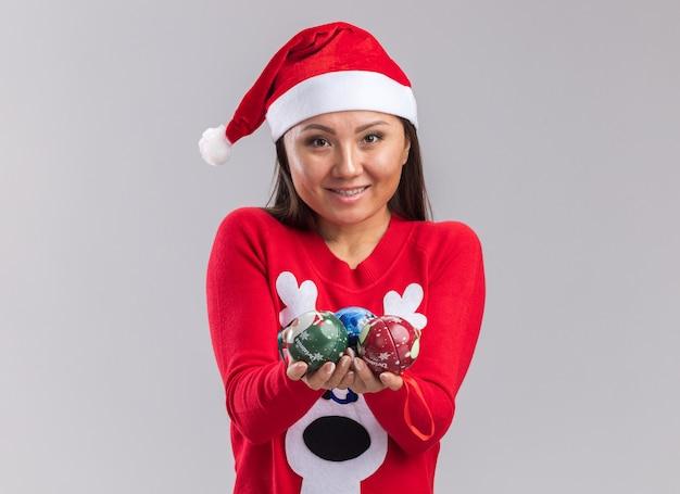 Lächelndes junges asiatisches mädchen mit weihnachtsmütze mit pullover, das weihnachtsbaumkugeln in die kamera hält, isoliert auf weißem hintergrund