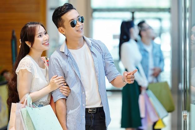 Lächelndes junges asiatisches paar mit einkaufstüten, das interessantes stück im schaufenster betrachtet