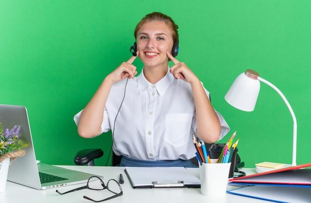 Lächelndes junges blondes callcenter-mädchen mit headset am schreibtisch sitzend mit arbeitswerkzeugen, die mit den fingern auf die wangen zeigen