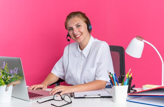 Lächelndes junges blondes callcenter-mädchen mit headset, das am schreibtisch mit arbeitswerkzeugen mit laptop sitzt sitting